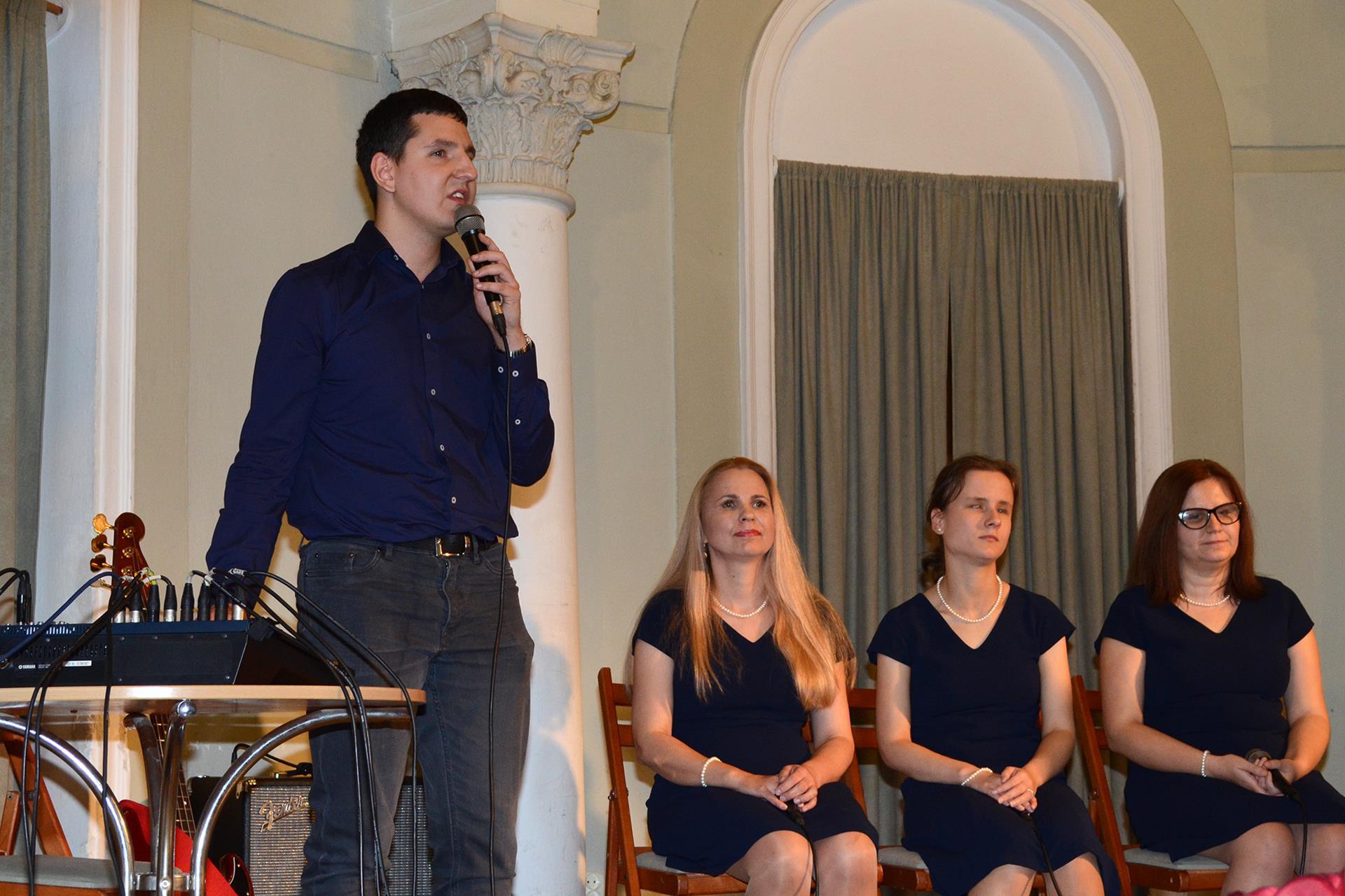 Mężczyzna stoi, śpiewa. Po jego lewej stronie siedzą trzy kobiety, ubrane są w granatowe sukienki.