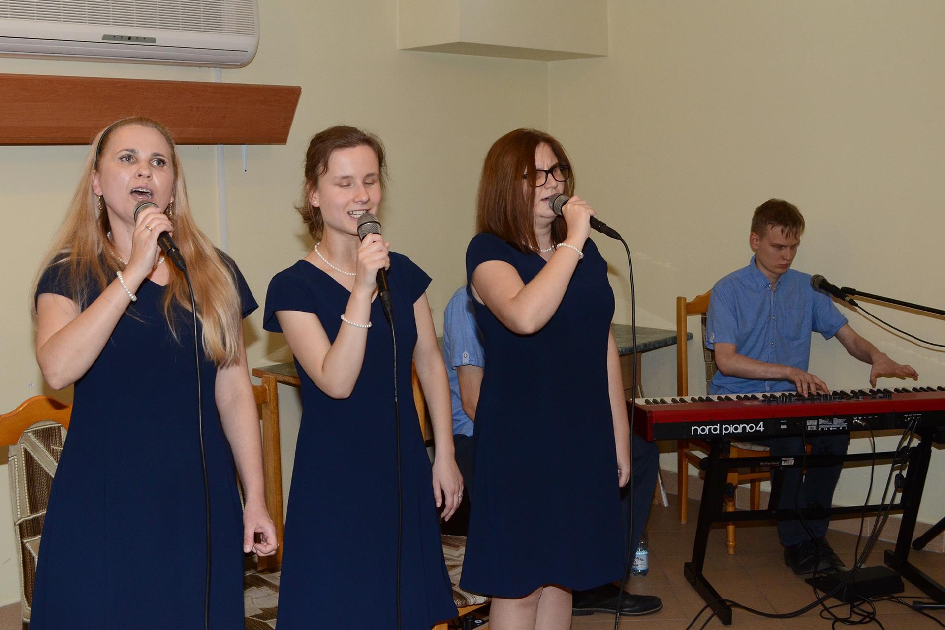 Trzy kobiety stoją, śpiewają. Na pianinie elektrycznym akompaniuje im mężczyzna.