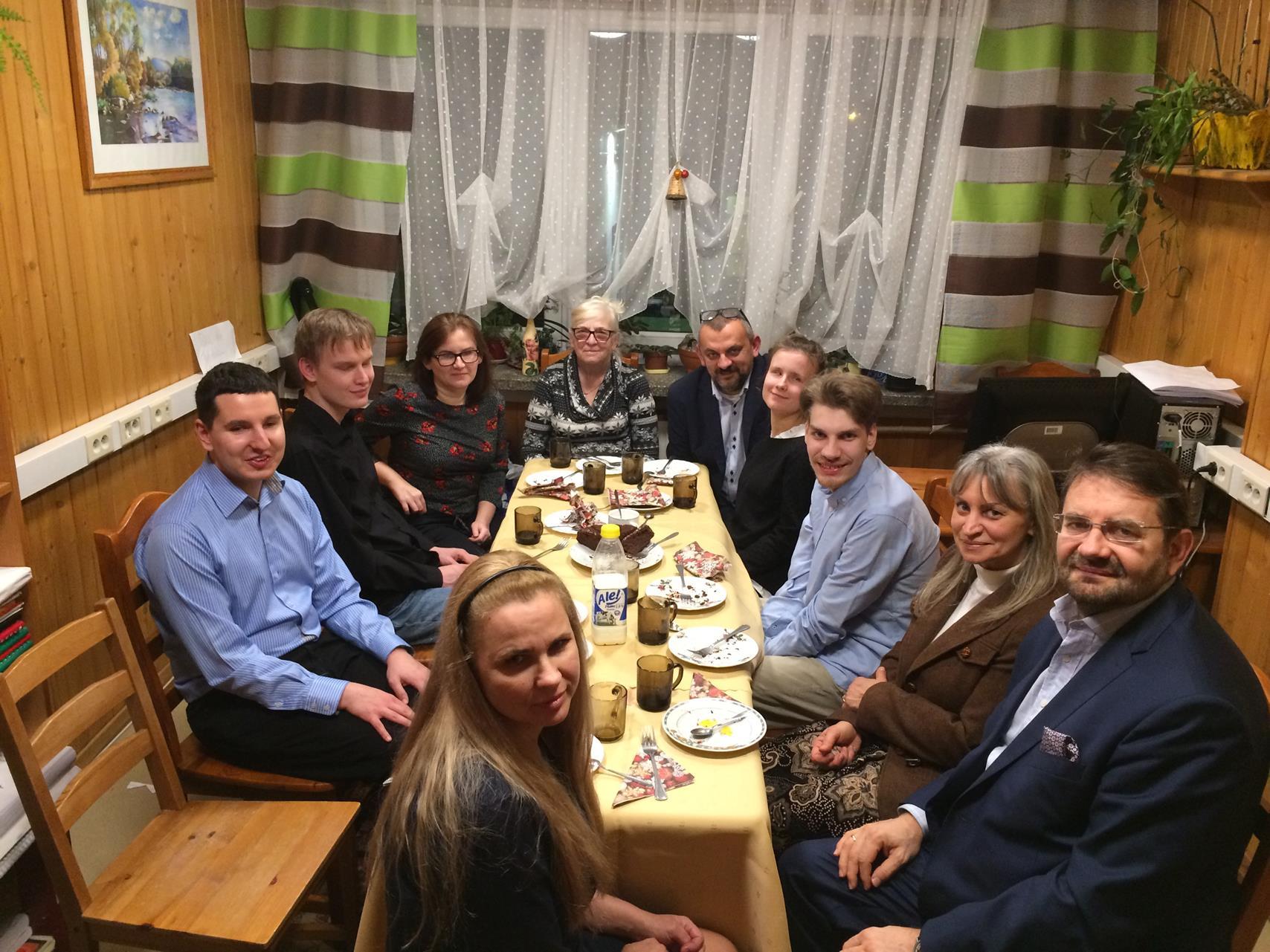 Przy stolę siedzi 10 osób, wszyscy się uśmiechają.