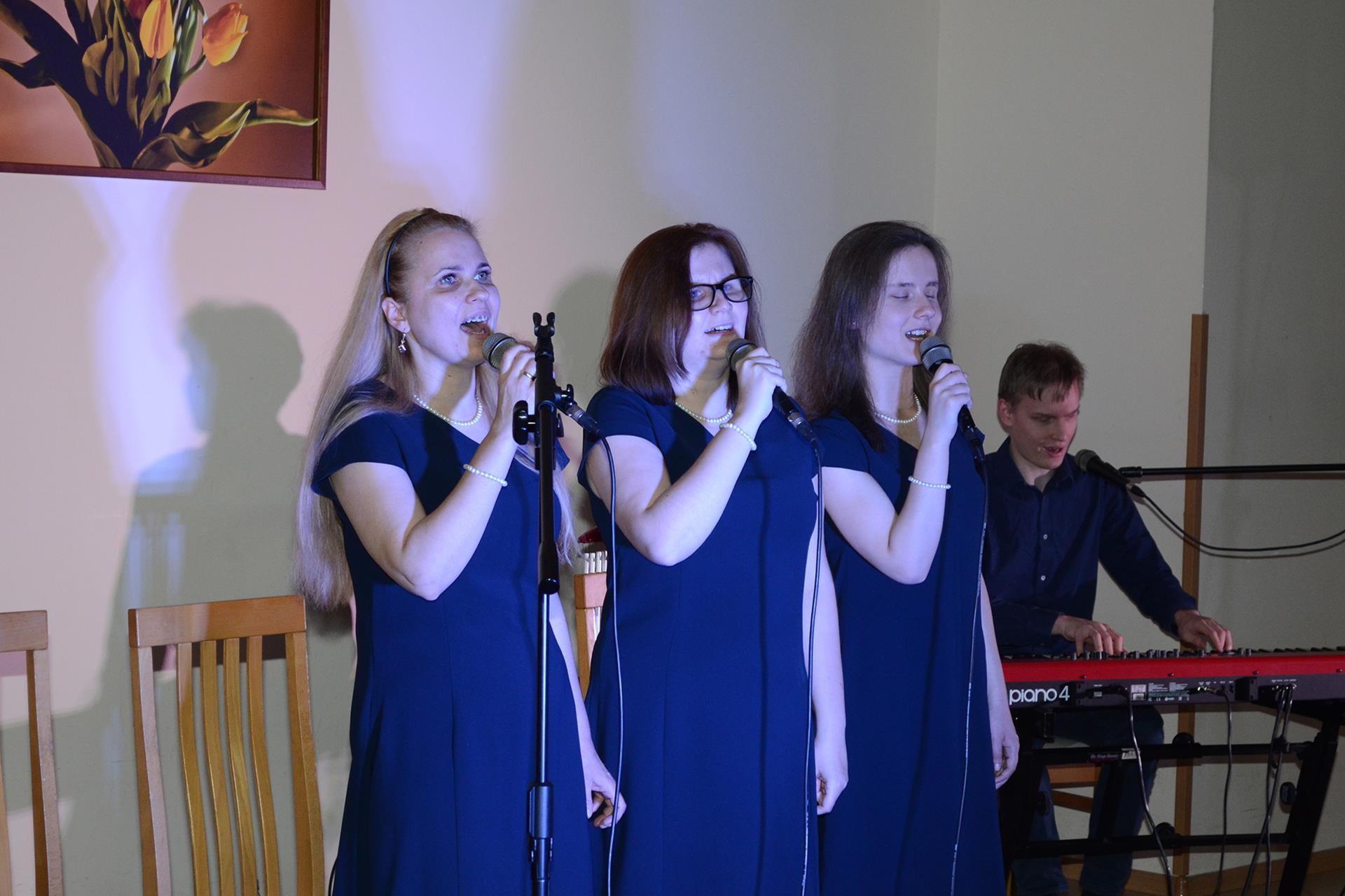 Trzy  kobiety śpiewają, towarzyszy im mężczyzna grający na pianinie elektrycznym.
