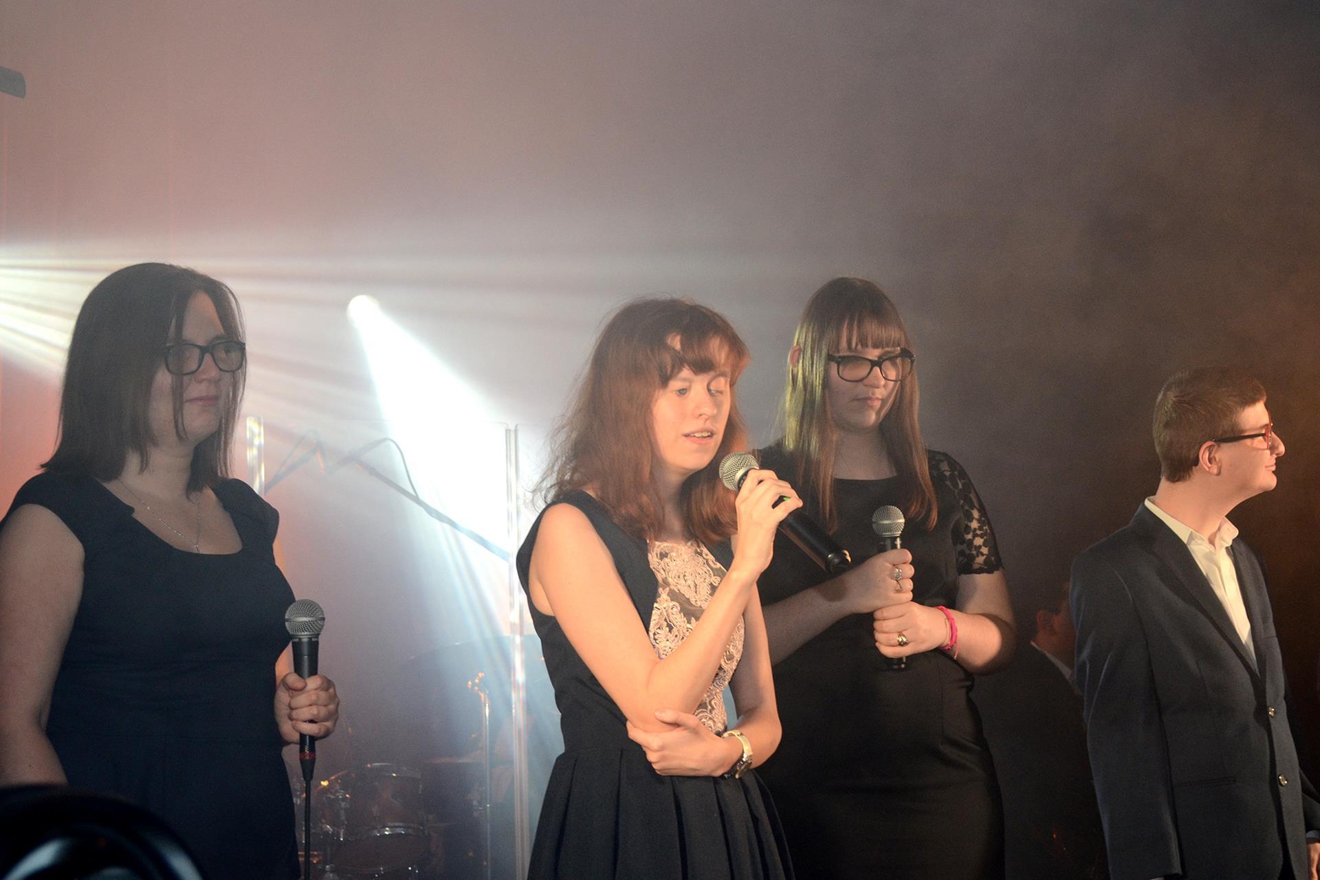 Cztery osoby stoją. 3 kobiety, 1 mężczyzna. Kobieta stojąca w środku śpiewa.