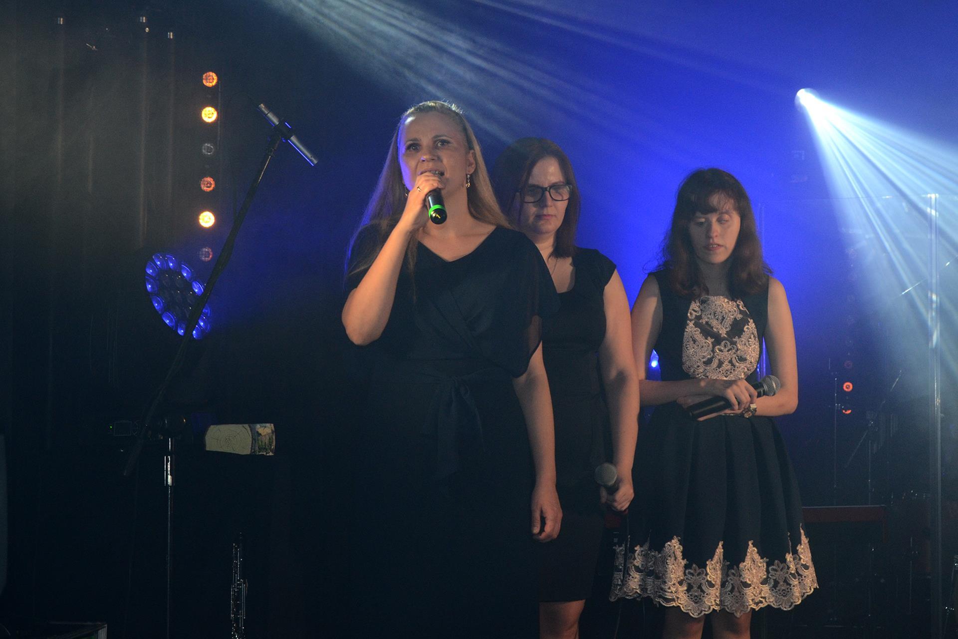 Kobieta śpiewa. Za nią stoją dwie kobiety.