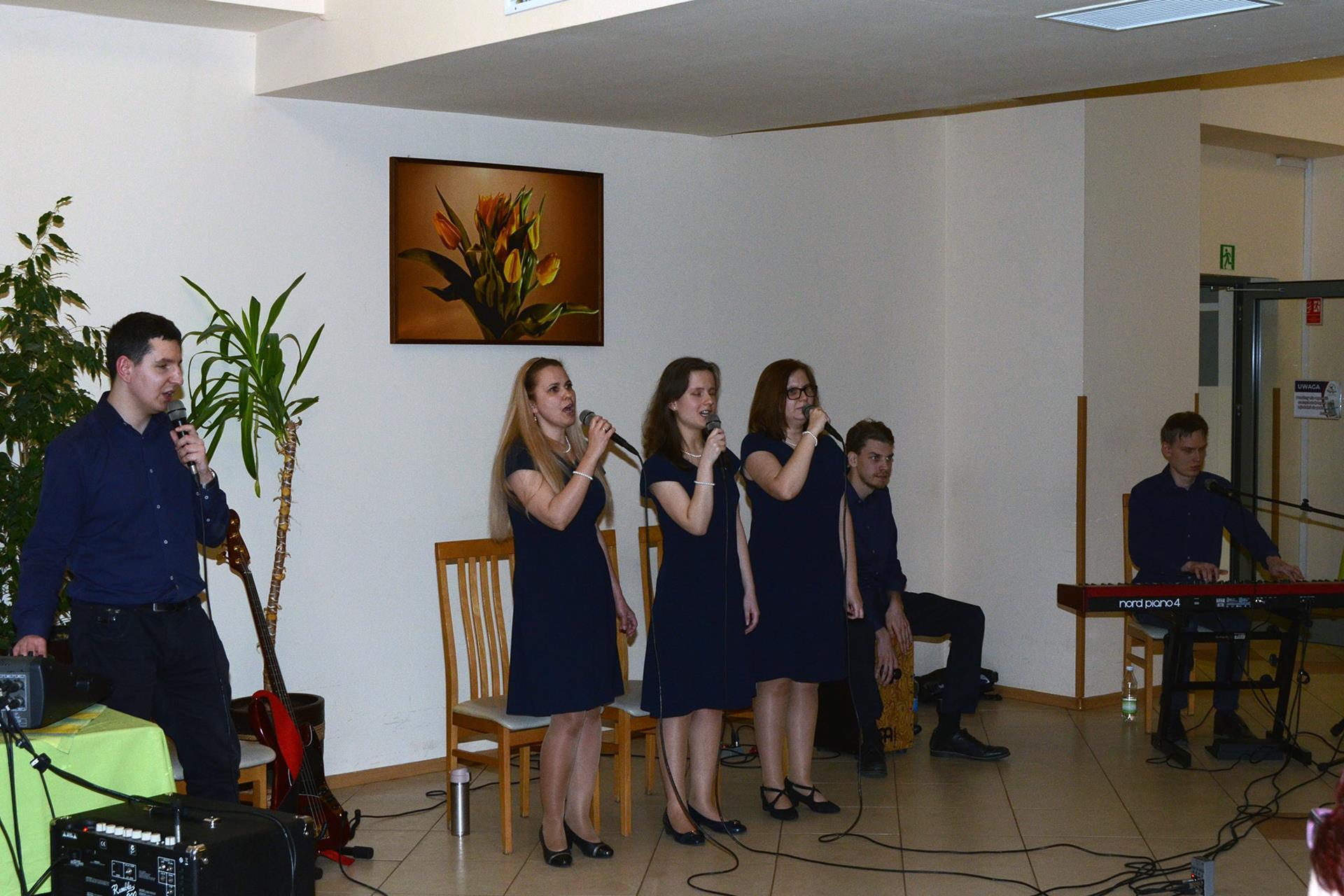 Trzy kobiety stoją, śpiewają. Po ich prawej stronie, przy mikserze, stoi mężczyzna, a po lewej dwóch mężczyzn gra na instrumentach - pianinie elektycznym i cajonie.