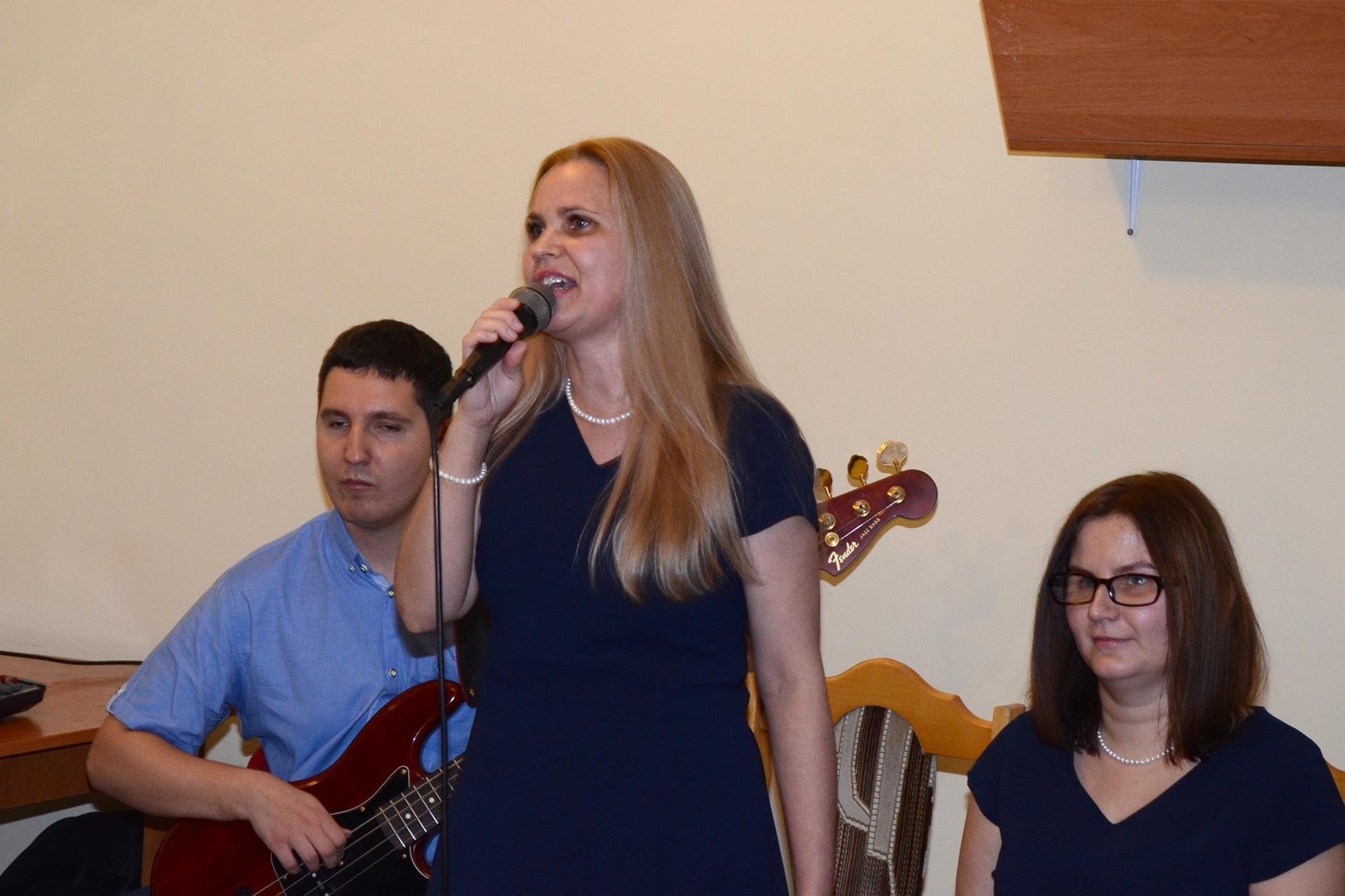 Kobieta śpiewa, po jej lewej stronie siedzi druga, a po prawej mężczyzna gra na gitarze basowej.