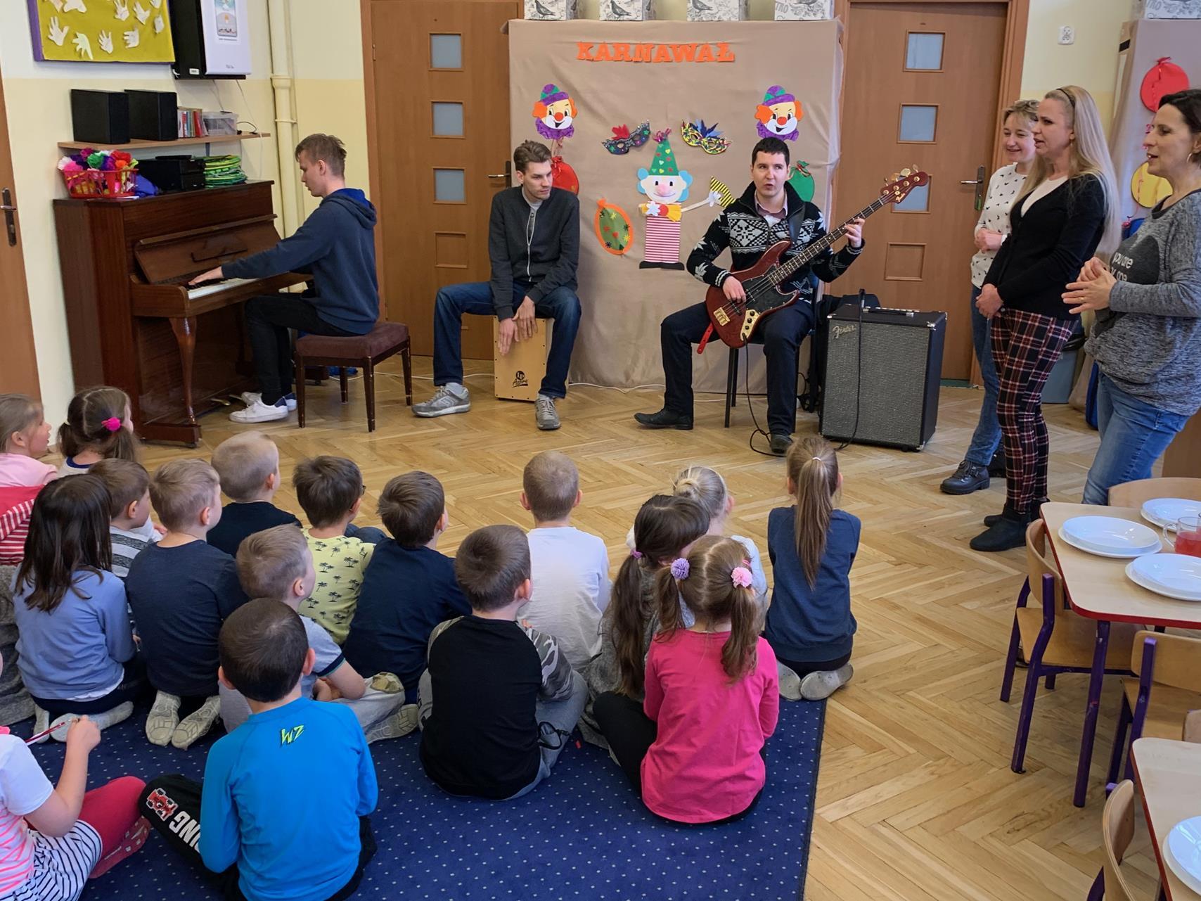 Kolorowa sala przedszkola. Trzech mężczyzn gra na instrumentach - pianino, cajon, gitara basowa, słuchają ich przedszkolaki siedzące na dywanie. Wszystkiemu przyglądają się trzy Panie, wśród których jest Prezes naszej fundacji.