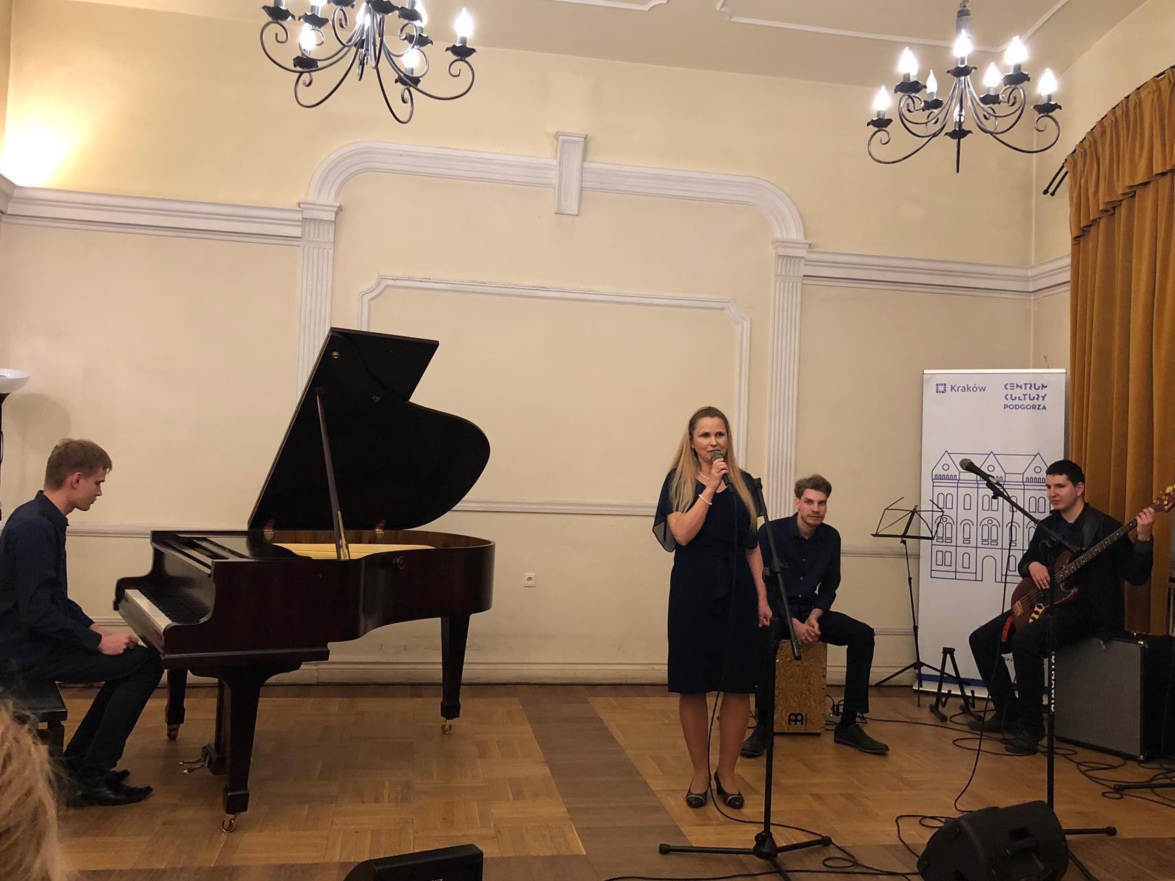 Kobieta przygotowuje się do występu, towarzyszy jej trzech mężczyzn grających na intrumentach: fortepian, cajon i gitara basowa