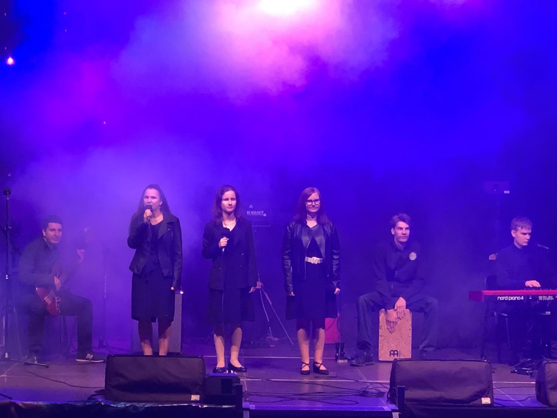 Na scenie znajduje się 6 osób (3 kobiety i 6 mężczyzn). Jeden mężczyzna gra na basie, drugi na cajonie, a trzeci na pianinie elektrycznym. Na środku sceny stoją kobiety, jedna z nich śpiewa.