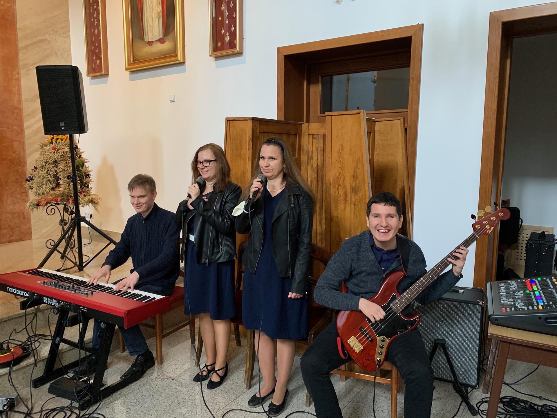 Cztery osoby (dwie kobiety i dwóch mężczyzn) znajdują się w kościele. Jeden mężczyzna gra na gitarze, a drugi na pianinie elektycznym. Kobiety stoją, w dłoniach mają mikrofony.