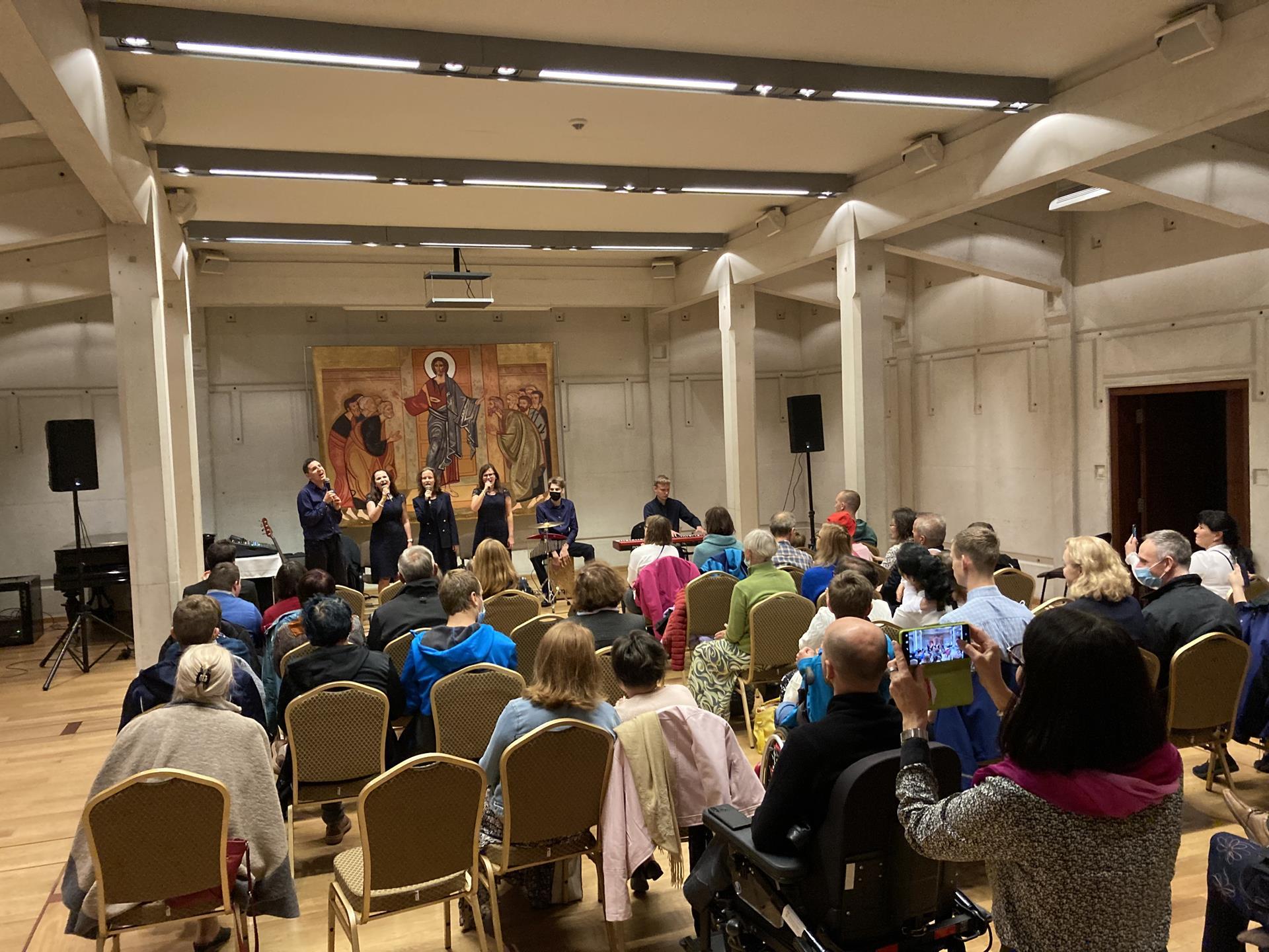 Zdjęcie z oddali. Publiczność słucha 6 osób, które grają i śpiewają.