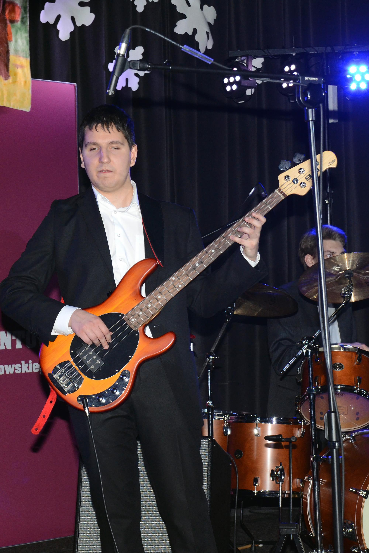 Adrian gra na gitarze basowej.