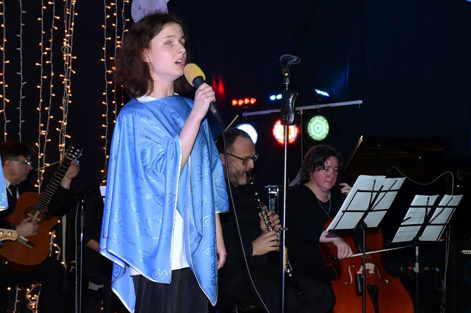 Natalia stoi, śpiewa.
